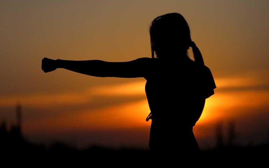 vrouw, gestrekte arm, ondergaande zon