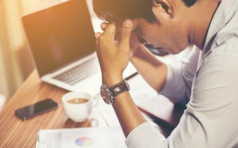 Man buigt zich bij zijn laptop over een statistiek rapport