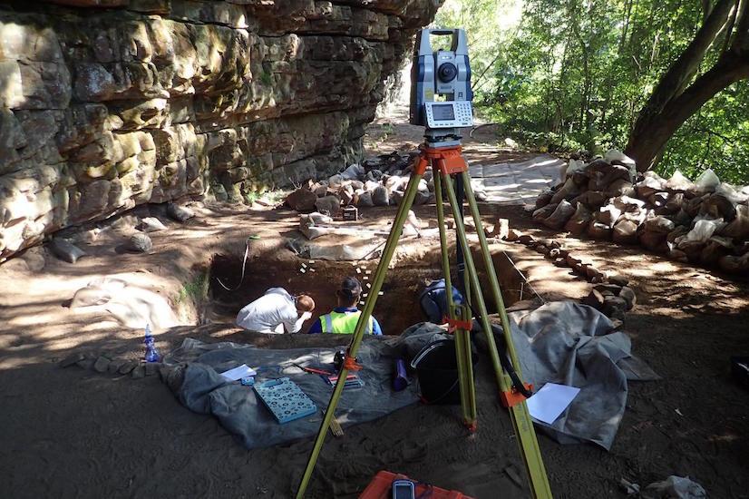 Veldwerk in Umhlatuzana, KwaZulu-Natal, Zuid Afrika. Op de voorgrond de theodoliet waarmee we de vondsten inmeten, erachter het team dat de stratigrafie (de opeenvolging van bewoningslagen) in de opgravingsput bestudeert.