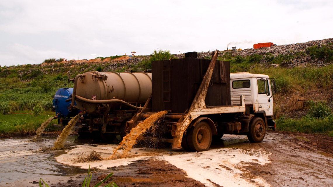 Truck loost inhoud latrines in een stabilisatievijver in Ghana